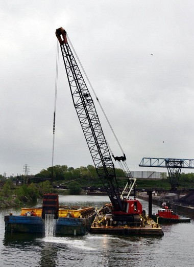 The U.S. Army Corps of Engineers supervises the dredging of six miles of Cuyahoga River sediment, twice per year, to maintain a depth of 23 feet.