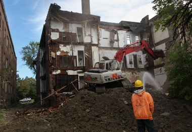 An excavator knocks down an apartment building on Superior Avenue in East Cleveland in September 2013. Today, there are still 140 vacant and blighted apartment buildings in the city.  (Gus Chan / The Plain Dealer)