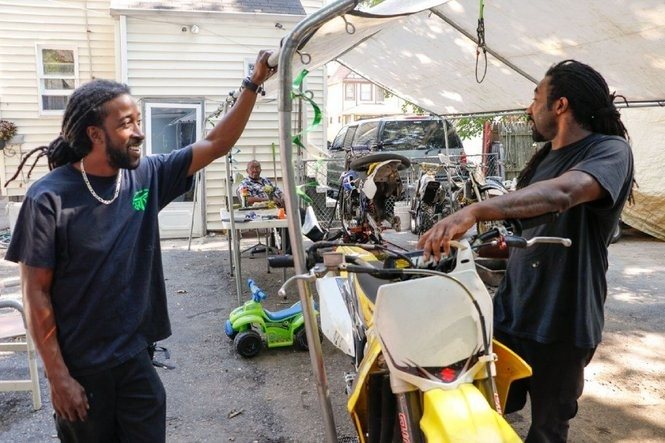 Johnnie Burton, left, and his cousin Dwayne, fix dirt bikes and visit with their grandfather, Bob Burton (background), in the Burton family backyard on East 93rd Street.