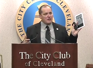 """Cleveland schools CEO Eric Gordon holds up a """"Nook"""" tablet computer at his 2012 State of the Schools address as he calls tablets and cell phones classroom """"game changers."""""""