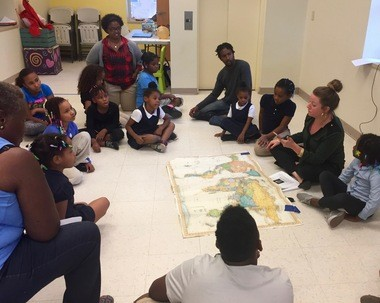 Program Director Faye Hargate sits with Brick City participants around a world map.