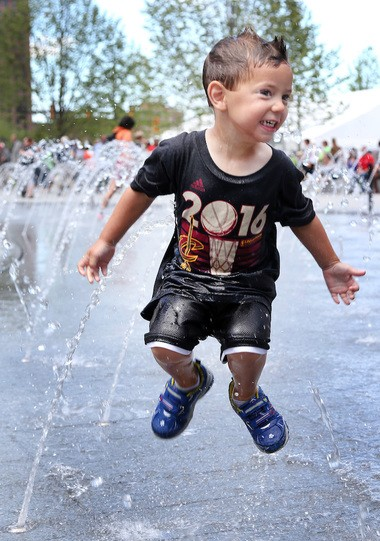 Jumping for joy at Public Square was 3-year-old Camden Kopkas of Strongsville, who was one of the first to run through the splash zone during the formal opening Public Square after a $50 million renovation in downtown Cleveland, Ohio on June 30, 2016. (Chuck Crow/The Plain Dealer)