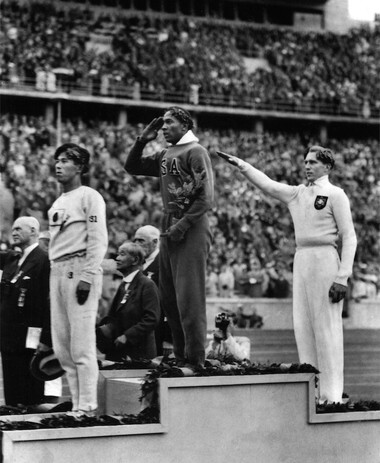 Cleveland Olympic hero Jesse Owens was among the visitors to the Great Lakes Expo. In this Aug. 11, 1936 file photo, Jesse Owens of the U.S., center, salutes during the presentation of his gold medal for the long jump, after defeating Nazi Germany's Lutz Long, right, during the 1936 Summer Olympics in Berlin. Naoto Tajima of Japan, left, placed third. (AP Photo, File)