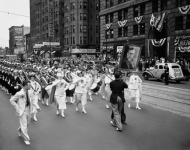 A bright spot in the Landon-for-President parade in Cleveland on June 11, 1936 through downtown streets and around the auditorium where the Republican National Convention is meeting was this drum corps of trimly clad girls. They strode down the street from the Landon hotel headquarters in military time, wearing large Landon sun flowers. (AP Photo)