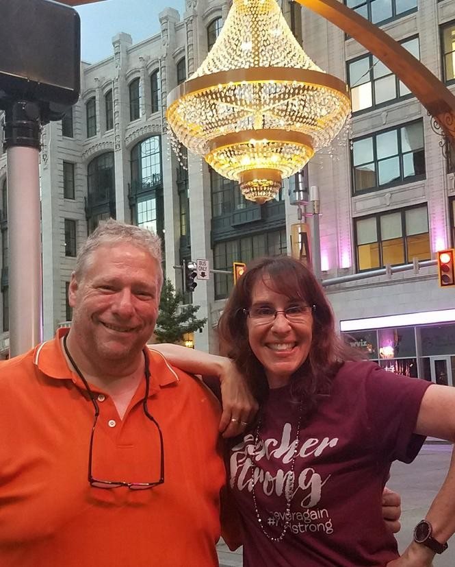 "Cleveland singer-songwriter Colin Dussault, who wrote the anti-gun anthem ""A Song for Our Children"" in an attempt to explain to his daughter how he felt about the Parkland, Florida, school shootings, poses with Ivy Schamis under the iconic chandelier at Playhouse Square. Schamis is a social studies teacher at Parkland's Marjory Stoneman Douglas High School. Two of her students died when bullets from an AR-15 reportedly wielded by former student Nikolas Cruz shattered windows in the door in the massacre that left 14 students and three adults dead on Valentine's Day of this year."