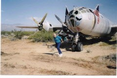 "Tony Mazzolini is shown in 1998 with the battered remains of ""Doc,"" the B-29 bomber once destined for use by the Navy for target practice. (Photo courtesy Tony Mazzolini)"
