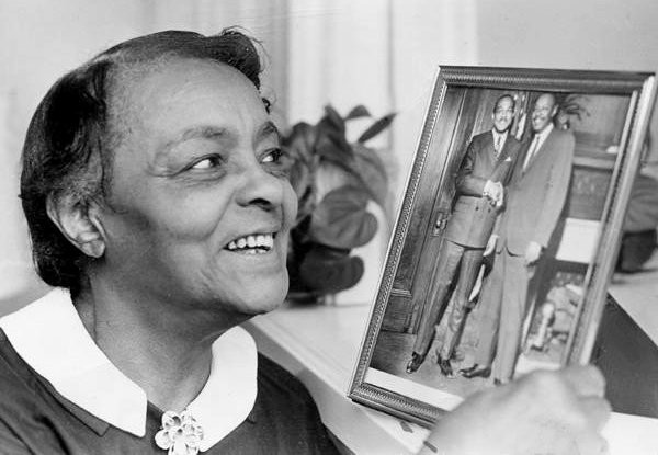 Louise Stokes, mother of Louis and Carl Stokes, admires a portrait of her sons. (Cleveland Press Collection, Clevelandmemory.org)
