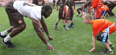 It's always a fun time when the Cleveland Browns and their fans get together, as is evident by the smiles on the faces of No. 1 pick Barkevious Mingo and a participant at Tuesday's youth football camp at FirstEnergy Stadium.