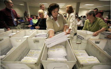 Kim O' Malley, a worker at the Cuyahoga County Board of Elections, sorts through the absentee ballots in May 2010. The Ohio House voted Wednesday to prohibit Cuyahoga and other counties from mailing unsolicited in-person absentee ballot applications.