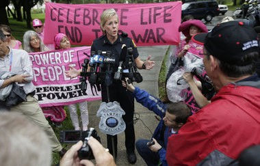 Then-Tampa Police Chief Jane Castor speaks to reporters as Code Pink protestors hold signs, Monday, Aug. 27, 2012, in Tampa.