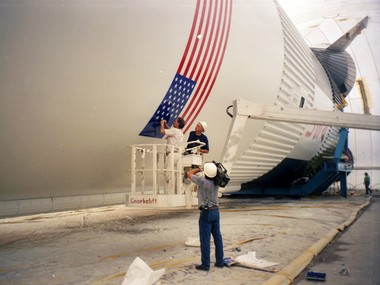 Workers paint the flag on the side of the Saturn V's massive first stage.