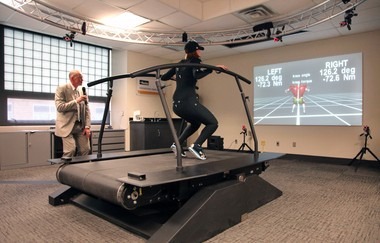 "As graduate student Sandy Hnat moves on a treadmill wearing a special motion-capture suit, Cleveland State University researcher Antonie ""Ton"" van den Bogert describes the computerized animation and data the lab produces."