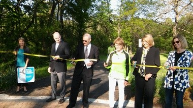 Cutting the ribbon at the May 18 Lake-to-Lakes trail connector dedication are, from left: Shaker Heights Principal Planner Ann Klavora; Shaker Councilman Tres Roeder; Mayor Earl Leiken; Cleveland Heights City Councilwoman and Heights Bicycle Coalition President Mary Dunbar; Shaker Councilwomen Nancy Moore and Anne Williams