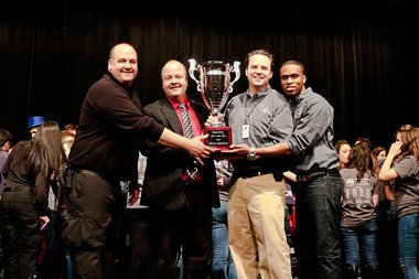 Solon Music in Motion directors, from left, Technical Director Joseph Ferencie, Assistant Director Ed Kline, Director Gary Lewis and Choreographer Antwon Chavis hold the Grand Champion trophy the show choir received at the Beavercreek Midwest Show Choir Classic.