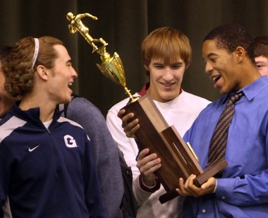 Kevin Burke (left), Mike Dinunzio (center) and Avery Bailey (right) check out St. Edward's 2010 Division I state championship trophy during a rally at the school on Dec. 6, 2010.
