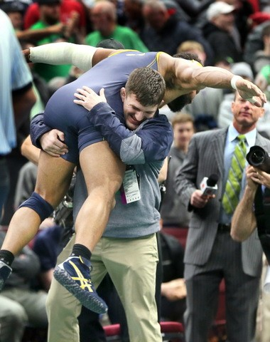 Kent State's Kyle Conel is lifted by assistant coach Matt Hill after Conel defeating Ohio State's Kollin Moore, 5-3, for third place at the 2018 NCAA Division I Wrestling Championships, Day 3, at Quicken Loans Arena in Cleveland, Ohio on March 17, 2018. It was the second time Conel defeated Moore in the tournament. (Chuck Crow/The Plain Dealer).