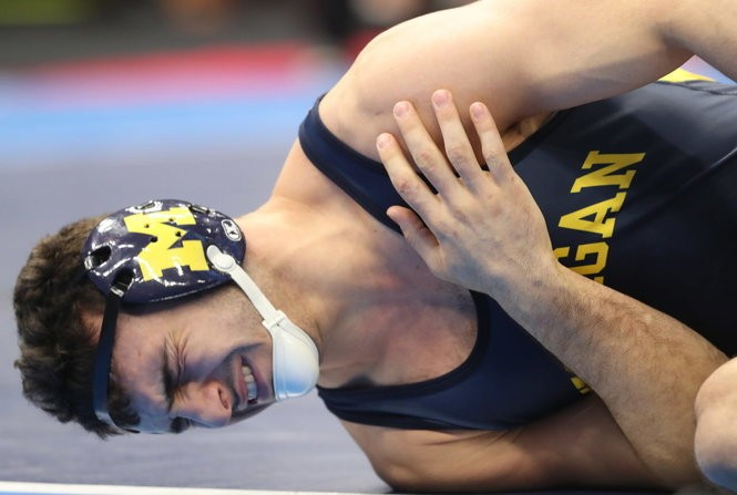 Domenic Abounader of Michigan has to take an injury timeout during his match against Emory Parker of Illinois during their consolation semifinal match at the 2018 NCAA Division I Wrestling Championships, Day 3, at Quicken Loans Arena in Cleveland, Ohio on March 17, 2018. (Chuck Crow/The Plain Dealer).