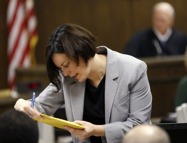 Prosecuting attorney Marianne Hemmeter, left, looks at evidence during the rape trial for a 17-year-old and 16-year-old in juvenile court on Thursday, March 14, 2013 in Steubenville, Ohio. The two are accused of raping a 16-year-old West Virginia girl in August of 2012. Presiding Judge Thomas Lipps is visible at right.