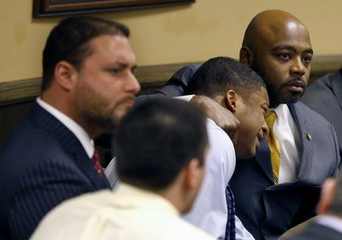Defense attorney Walter Madison, right, holds his client, 16-year-old Ma'lik Richmond, second from right, while defense attorney Adam Nemann, left, sits with his client Trent Mays, foreground, 17, as Judge Thomas Lipps pronounces them both delinquent on rape and other charges after their trial in juvenile court in Steubenville.
