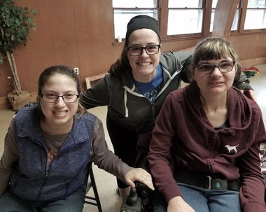 River Rock participants Becky Sweet, left, and Rachel Nagy, right, are all grins with staff member Kaitlyn Metcalf, center, after playing games on a rainy day.