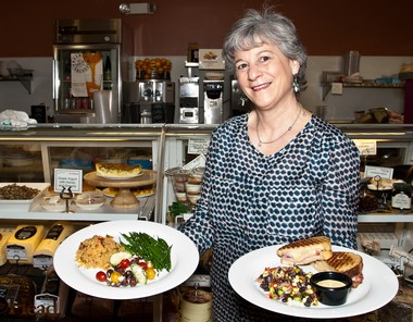 Joan Pistone holds southwest roasted vegetable couscous, Greek village salad and green beans, left, and a panini with Black Forest smoked ham, gruyere and Dijon-thyme aioli.
