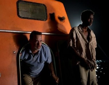 All hands on deck: Hanks, as the title character, and one member in a small band of Somali pirates, emerge from a lifeboat.