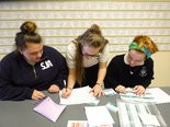 Seniors Emily Tehorik, from left, Emily Hanes and Kendra Golak, all of Cleveland, check the ticket list at the fundraiser.
