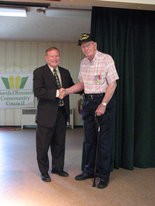 North Olmsted Mayor Mayor Kevin Kennedy congratulates World War II veteran Thomas Edward Devries Jr. after presenting him with service awards. Photo provided by North Olmsted Senior Center.