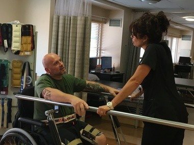 Before embarking on the hard work of standing and walking, Billy Ottinger discusses the day's physical therapy game plan with MetroHealth's Darcy Kosmerl.