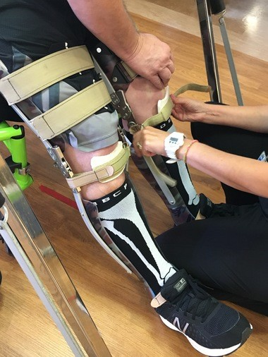 Physical therapist Darcy Kosmerl adjusts the straps on Billy Ottinger's KAFO (knee-ankle-foot-orthosis) braces.