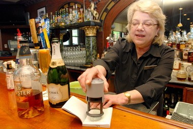 Bartender Cindy Kebbell stamps an Urban Bourbon Trail passport at the Old Seelbach Bar in Louisville's emerging SoFo (South Fourth) district.