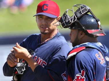 Cleveland Indians pitcher Carlos Carrasco talks with catcher Carlos Santana in the first inning in a split-squad game against the Milwaukee Brewers Sunday, in Phoenix.