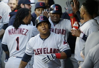 Cleveland Indians' Jose Ramirez, front, and Juan Uribe, upper center, are greeted in the dugout after Uribe scored Ramirez with a sacrifice fly in the fourth inning of Monday's 3-1 victory over the Mariners in Seattle.