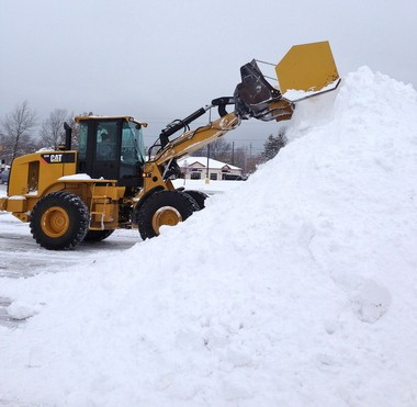 A front-end loader clears snow Monday from the parking lot of Super Kmart in Mentor. Crews will be back at work again this morning as snow continues to fall in eastern counties, with predictions of up to 3 feet in some areas by Wednesday morning.