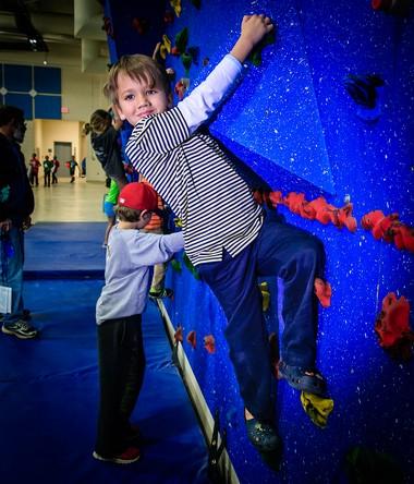 Cooper Kernicki, 6, of Bainbridge climbs a wall during Kenston's recent Play Blue day.
