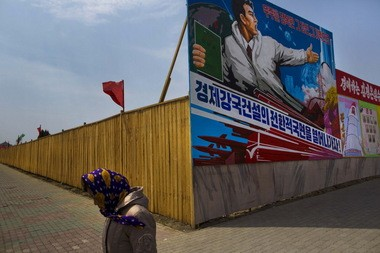 """A North Korean woman walks past a construction site where a propaganda billboard depicts the launch of North Korean rockets in Pyongyang, North Korea on Saturday, April 13. The billboard reads: """"Let's open up an era to a strong economic country."""""""