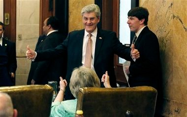 Gov. Phil Bryant and fellow Republican, Rep. Wanda Jennings of Southaven, seated, celebrate passage of several of the governor-backed education bills, Tuesday, April 2, 2013 in House Chambers at the Capitol in Jackson, Miss. The governor monitored the bills debate in his office at the Capitol and came to the floor to show his gratitude to their supporters. (AP Photo/Rogelio V. Solis)