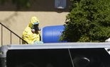 A hazardous material cleaner removes a blue barrel from the apartment in Dallas, Friday, Oct. 3, 2014, where Thomas Eric Duncan, the Ebola patient who traveled from Liberia to Dallas stayed last week. The family living there has been confined under armed guard while being monitored by health officials. (AP Photo/LM Otero)