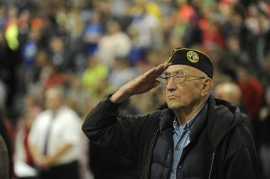 In this photo taken Tuesday, Nov. 10, 2015, George Case, a veteran of the U.S. Army who served in the South Pacific and Panama, salutes a U.S. Coast Guard Color Guard procession at the end of the Veterans Day assembly at Sunset Middle School in Coos Bay, Ore. Students honored local veterans with speeches, and band and choir performances. (Amanda Loman/The World via AP)