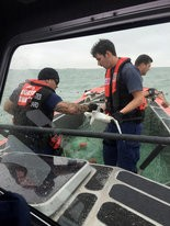 In this photo released by the U.S. Coast Guard, a boat crew frees a shark from an illegal net Tuesday, Dec. 1, 2015.