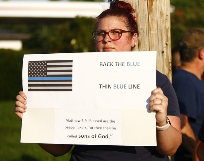 Sarah Schmidt, of South Whitehall, silently protests across the street as people gather near the corner of Lincoln Avenue and Hamilton Boulevard in South Whitehall on Aug. 1, 2018, to protest the shooting death of Joseph Santos by a township police officer. The shooting took place on July 28, 2018, just outside the Dorney Park. (Saed Hindash | For lehighvalleylive.com)