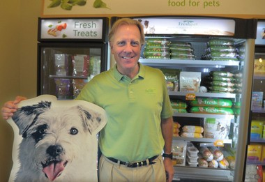 Freshpet CEO Richard Thompson stands in front of a display of his company's products. The Freshpet line uses fresh ingredients and no preservatives.