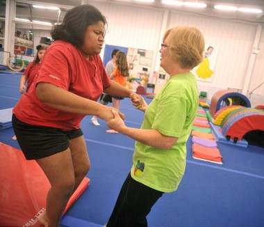 Coach Casey Skoglund, right, works with Simone Williams, 33, of Bethlehem, during training Thursday at Parkettes Gymnastics in Allentown for the 2014 Special Olympics USA Games.