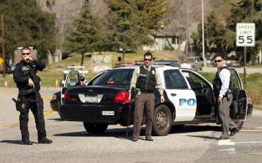 Police block a road this afternoon at Yucaipa, Calif., as a gunfight between police and fugitive ex-Los Angeles cop Christopher Dorner takes place farther up the highway near Big Bear Lake.