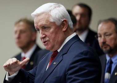Pennsylvania Gov. Tom Corbett, center, stands with a group of colleagues during a news conference as he addresses his plan to privatize the liquor system Jan. 30 in Pittsburgh.