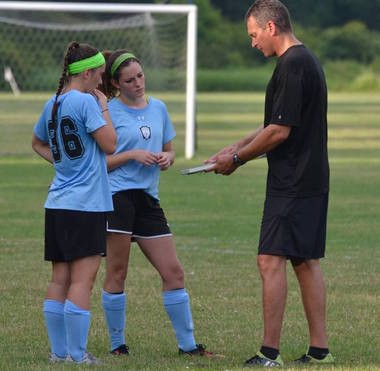 George Denger on the field with two of the players he coaches. (Courtesy photo)