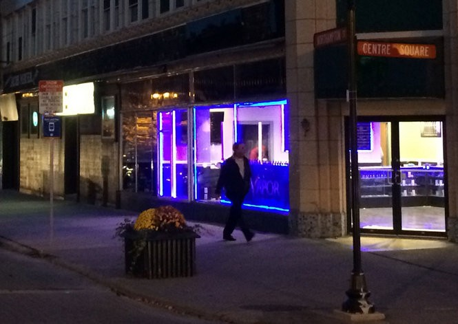 A man walks by Premier Vapor in Centre Square at dusk Oct. 26, 2015. Easton Mayor Sal Panto Jr. is not a fan of the new store's blue neon in the window. (Kurt Bresswein | For lehighvalleylive.com)