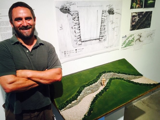 "Paul Deery poses with a model of his sculpture ""Waterway."""
