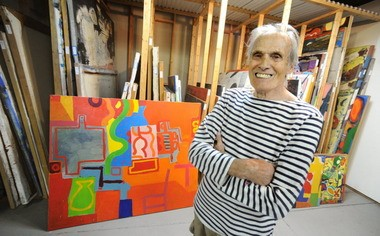 Artist Bill Barrell poses in front of his collection of paintings at his Bullseye Art studios in Easton.