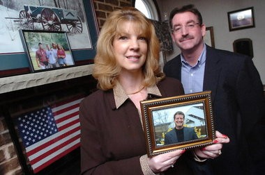 Karen Bush and Joe Douress pose in this 2008 photo with a photo of Barry Bush, the FBI special agent killed in 2007 during a bank robbery. The American flag in the background flew at the site were Bush was killed.